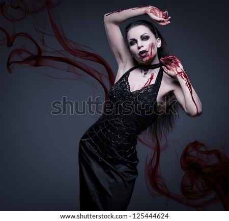 Beautiful vampire woman covered in blood - stock photo