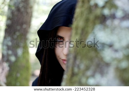 beautiful vampire woman hidden behind a tree in the forest - stock photo