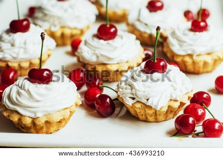 Beautiful  vanilla cupcakes with white protein cream and cherry on top. cake Shot on wooden table. currant muffin   - stock photo