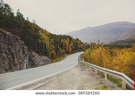 Beautiful vibrant fall autumn landscape of national park near border of Finland, Sweden and Norway, with mountains, camping place, road and forest - stock photo