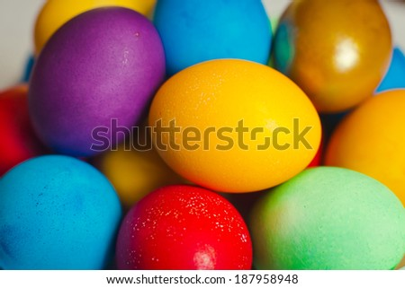 Beautiful vibrant multi-colored plate easter eggs for easter coloured in gold blue yellow green purple - stock photo