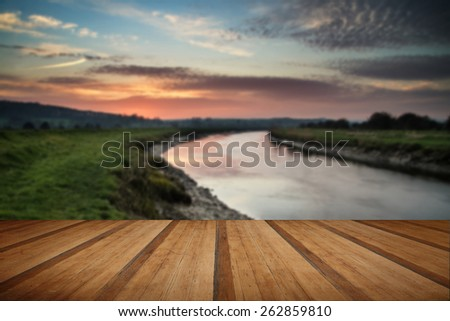 Beautiful vibrant sunrise reflected in calm river  with wooden planks floor - stock photo