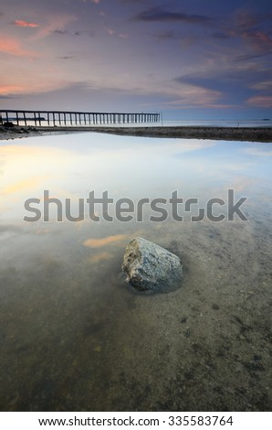 Beautiful vibrant  sunset over abandoned pier at sea - stock photo