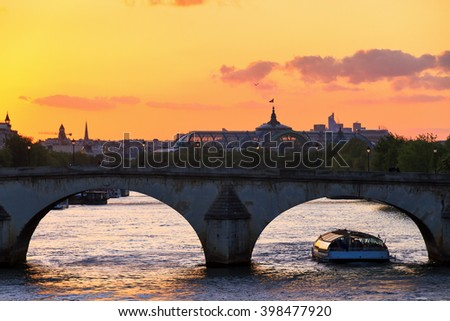 Beautiful vibrant sunset over the river Seine in Paris, France, with a tourist canalboat under an arched bridge and the Grand Palais in the background - stock photo