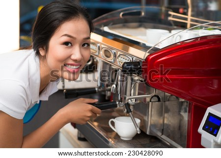 Beautiful Vietnamese barista making cup of coffee with a machine - stock photo