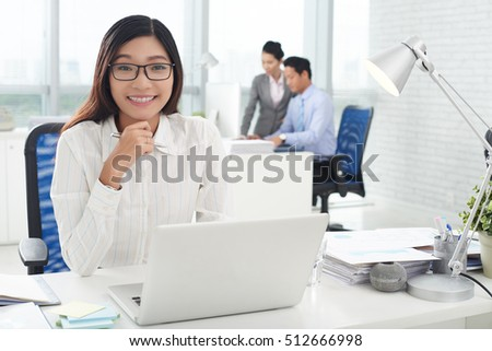 Beautiful Vietnamese business executive smiling and looking at camera