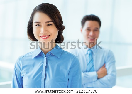Beautiful Vietnamese business lady and her male collegue in background - stock photo