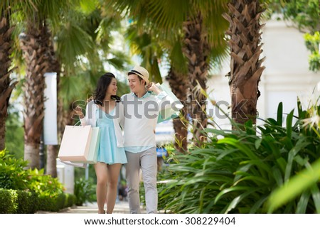 Beautiful Vietnamese couple in love walking in the park after shopping - stock photo