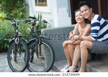 Beautiful Vietnamese couple resting on the porch after biking - stock photo