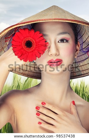 Beautiful vietnamese girl in a traditional hat is holding flower - stock photo