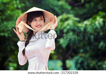 beautiful Vietnamese girl in traditional long dress ( Ao Dai ) with conical hat. - stock photo