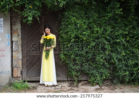 Beautiful vietnamese girl with traditional dress (ao dai) and daisy flowers in Hanoi, Vietnam