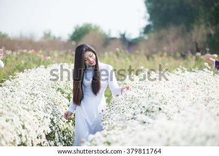 Beautiful Vietnamese girl with traditional dress (ao dai) is in white daisy flower garden in Hanoi, Vietnam