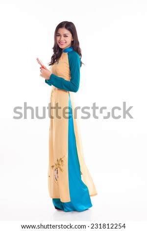 Beautiful Vietnamese woman with ao dai holding lucky red packet for celebrate lunar new year on white background - stock photo