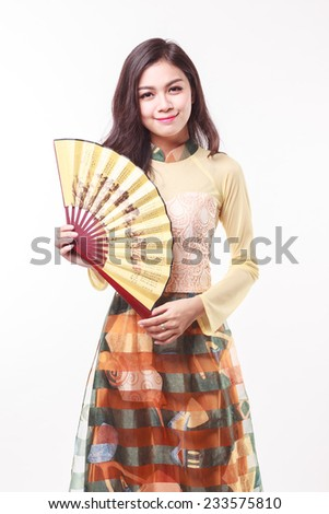 Beautiful Vietnamese young woman with modern style ao dai holding a paper fan on white background  - stock photo