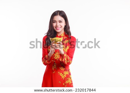 Beautiful Vietnamese young woman with red ao dai holding lucky new year ornament - stack of gold on white background  - stock photo