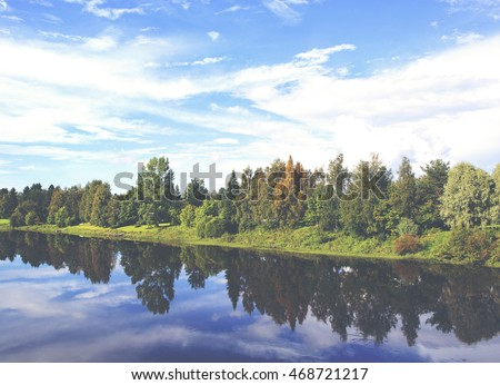 Beautiful view at the bridge. Boats and forest are reflecting from the water on a sunny evening in Finland. Image has a vintage effect applied.