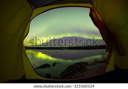 Beautiful View from the tent on the northern lights - stock photo