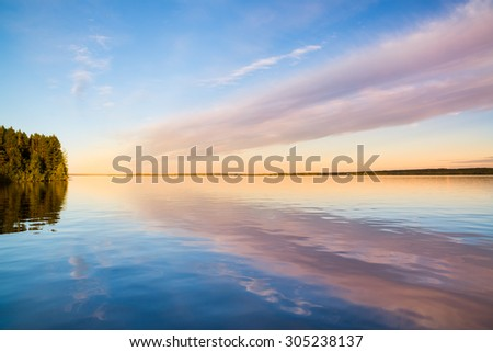 beautiful view of a blank lake with reflection of clouds and a clear sky
