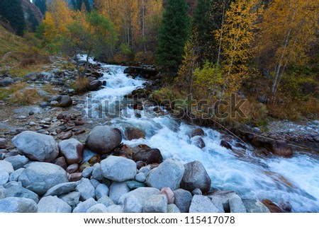 Beautiful view of a mountain river with colored trees - stock photo