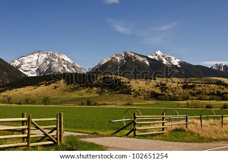 Beautiful view of a piece of a ranch with snowy mountains as a backdrop on a spring day - stock photo