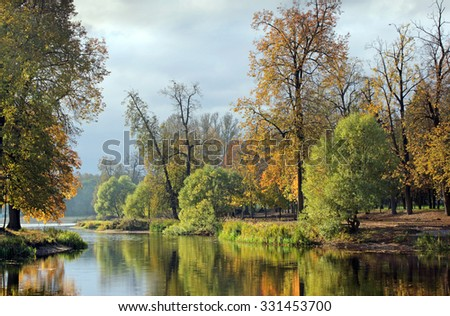 Beautiful view of a small lake edged by green trees at autumn cloudy evening. - stock photo