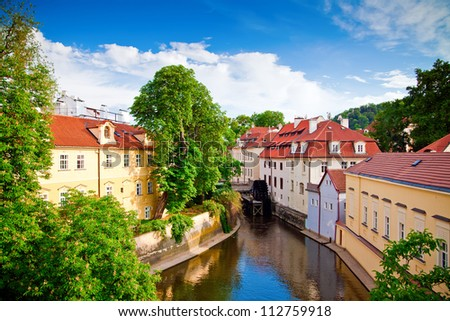 beautiful view of a street with old water mill in a canal in center of Prague - stock photo