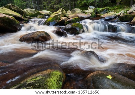 Beautiful view of an autumn wild waterfall. - stock photo