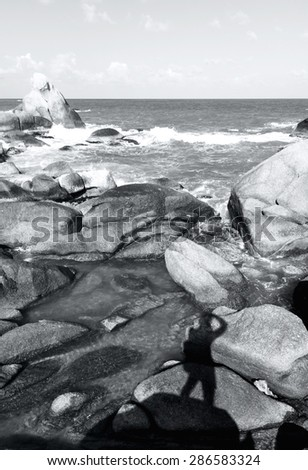 beautiful view of coastline stones, ocean waves and a photographer silhouette. summer trip adventure - stock photo