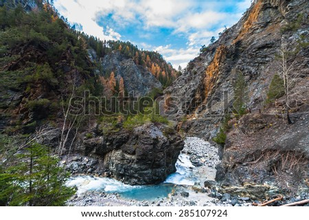 Beautiful view of creekrunning in canyon on the hiking path in autumn, near Scuol in Grisons, Switzerland - stock photo