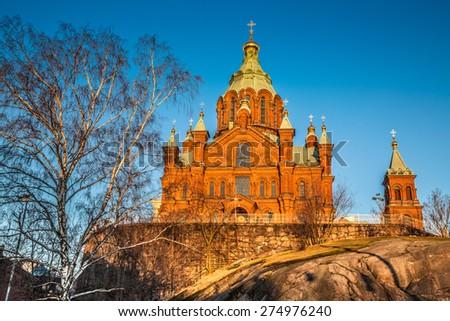 Beautiful view of famous Eastern Orthodox Uspenski Cathedral (Uspenskin katedraali) on a hill in the golden evening light on Katajanokka peninsula, Helsinki, Finland - stock photo