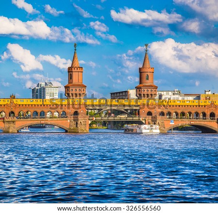 Beautiful view of famous Oberbaum Bridge at Spree river with excursion boat and Berliner U-Bahn tram on a sunny day with blue sky and clouds in summer, Berlin Kreuzberg-Friedrichshain, Germany - stock photo