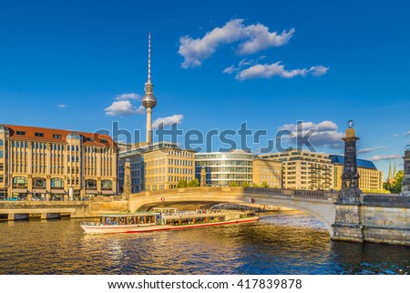 Beautiful view of famous TV tower and historic buildings at Museum Island with boat passing Friedrichsbruecke on Spree river in golden evening light with blue sky at sunset in summer, Berlin, Germany - stock photo