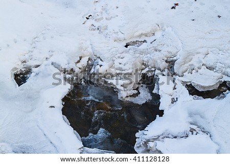 Beautiful view of flowing water under ice in winter - stock photo