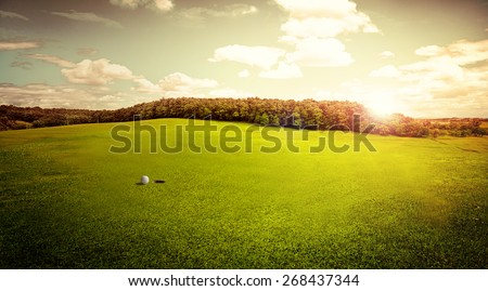 Beautiful view of green golf field with ball and hole at sunrise in the morning. Hobby, leisure and activity concept. Golf ball on lip of cup. - stock photo