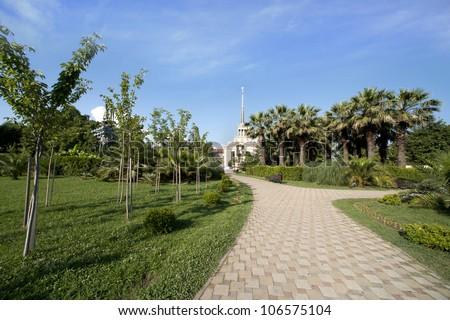 Beautiful view of green tropical park with palm trees about building of a seaport of Sochi (Russia) - stock photo
