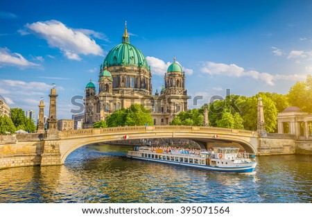 Beautiful view of historic Berlin Cathedral (Berliner Dom) at famous Museumsinsel (Museum Island) with excursion boat on Spree river in beautiful evening light at sunset in summer, Berlin, Germany