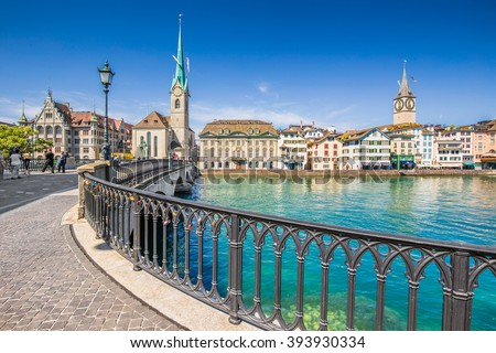 Beautiful view of historic city center of Zurich with famous Fraumunster Church and Munsterbucke crossing river Limmat on a sunny day with blue sky and clouds in summer, Canton of Zurich, Switzerland - stock photo