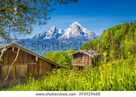 Beautiful view of idyllic mountain scenery in the Alps with traditional old mountain chalet and fresh green meadows in springtime - stock photo
