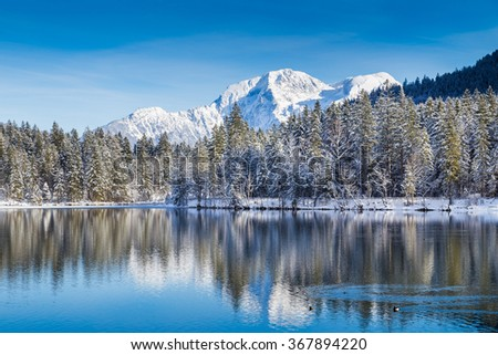 Beautiful view of idyllic winter wonderland with crystal clear mountain lake in the Alps on a cold sunny day with blue sky and clouds, Nationalpark Berchtesgadener Land, Upper Bavaria, Germany - stock photo