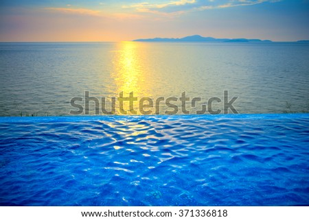 Beautiful view of Infinity Swimming Pool with sunset on the sea at twilight times. - stock photo