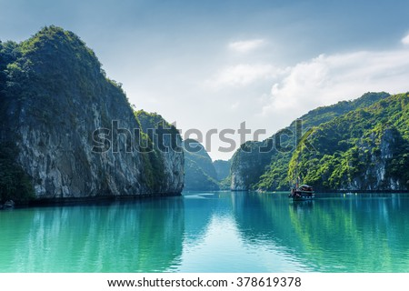 Beautiful view of lagoon in the Halong Bay (Descending Dragon Bay) at the Gulf of Tonkin of the South China Sea, Vietnam. Landscape formed by karst towers-isles on blue sky background. - stock photo