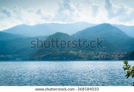 beautiful view of lush green mountains disappearing into the distance at Lake Como in Italy - stock photo