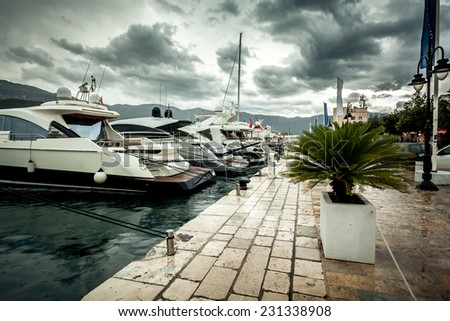 Beautiful view of moored luxurious yachts at cloudy and rainy day - stock photo