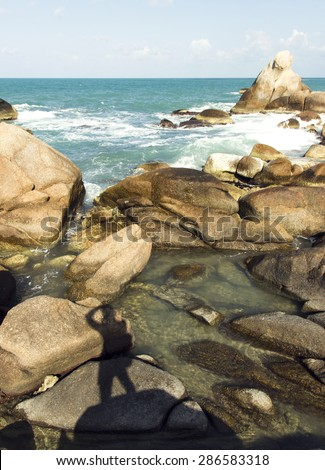 beautiful view of ocean waves and man silhouette on the rocks. summer trip adventure - stock photo