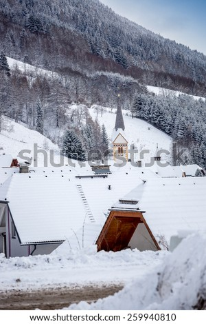 Beautiful view of old high belfry at traditional Alpine village - stock photo