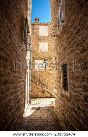 Beautiful view of old narrow street with high buildings at sunny day - stock photo
