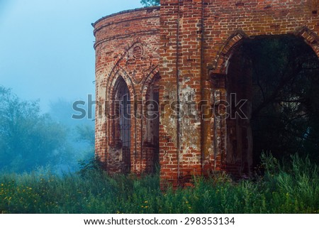 Beautiful view of old ruined red bricks castle with arches at summer green grass and deep fog background. - stock photo