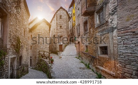 Beautiful view of old traditional houses and idyllic alleyway in the historic town of Casso, Friuli, Italy