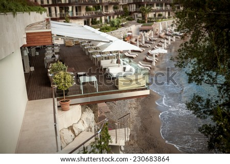Beautiful view of restaurant with summer terrace on high cliff at Mediterranean sea - stock photo
